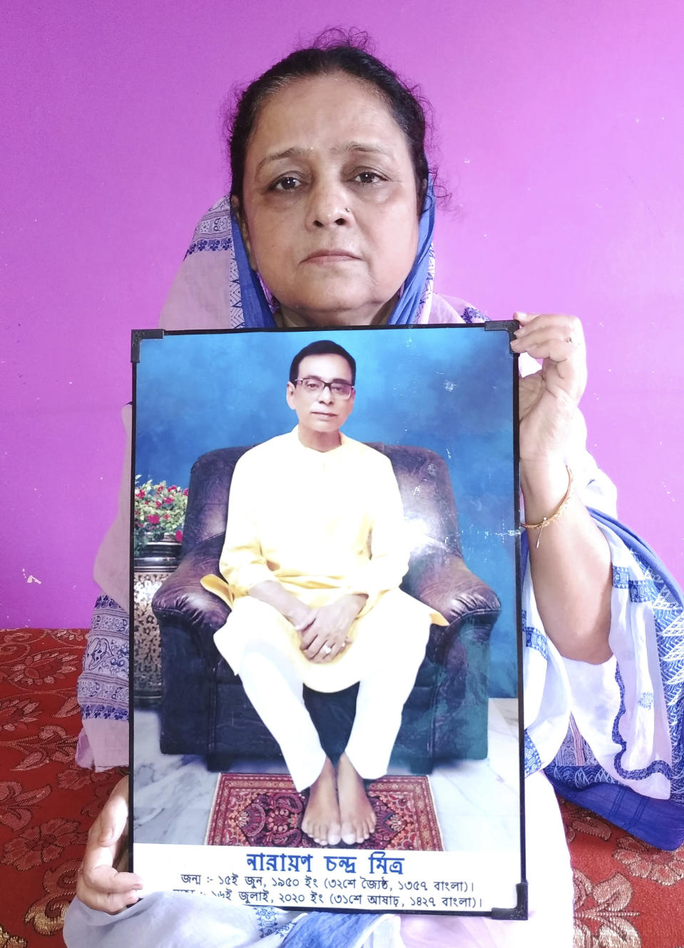 Anindita Mitra, 61, poses with a portrait of her husband late Narayan Mitra, at her house in Silchar, India, Sunday, Sept. 13, 2020. Narayan Mitra, wasn't listed among those killed by the coronavirus that authorities put out daily because the test results confirming COVID-19 arrived after his death. In India, people who die with other preexisting conditions are often not counted as COVID-19 deaths, while only those who test positive for the virus before dying are included in the official tally in many states. (AP Photo/Joy Roy)
