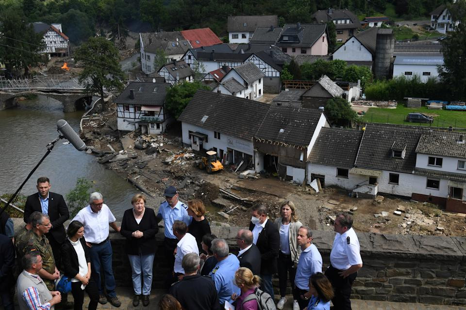 German Chancellor Angela Merkel and Rhineland-Palatinate State Premier Malu Dreyer speak to people as they stand on a bridge during their visit in the flood-ravaged areas, in Schuld near Bad Neuenahr-Ahrweiler, Rhineland-Palatinate state, Germany, July 18, 2021. Christof Stache/Pool via REUTERS