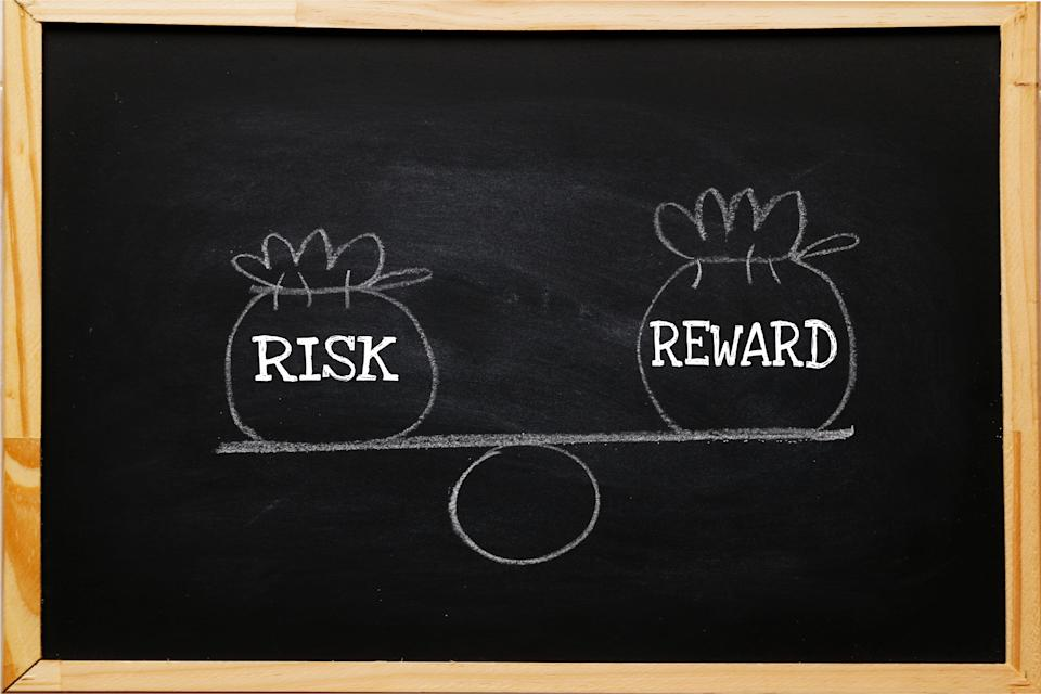 Write symbol Risk and reward bags on a basic balance scale in equal position on blackboard. risk management concept, depicts investors use a risk reward ratio to compare the expected return of an investment