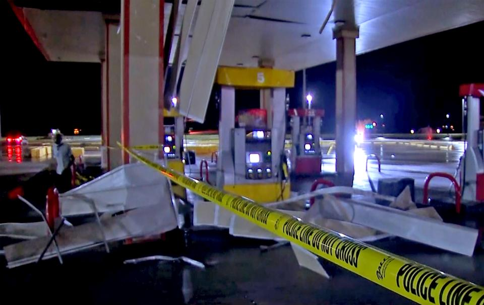 In this image made from video, debris from tornadoes pile around the pumps of a filling station late Sunday, Oct. 10, 2021, in Shawnee, Oklahoma.