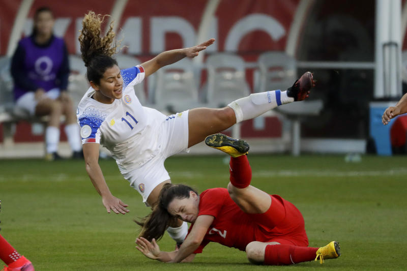 FILE - In this Feb. 7, 2020, file photo, Costa Rica forward Raquel Rodriguez, top, is knocked over by Canada defender Allysha Chapman during the first half of a CONCACAF women's Olympic qualifying soccer match in Carson, Calif. Raquel Rodriguez, better known as Rocky to her fans, was in route to join her new National Women's Soccer League team when sports were shut down by the coronavirus.  It certainly wasn't an ideal start for the Costa Rican striker with the Portland Thorns. (AP Photo/Chris Carlson, Fle)