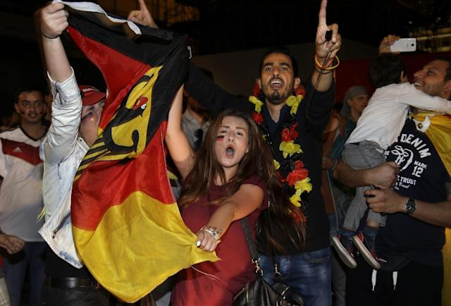 Supporters of the German national soccer team wave German flags while they celebrate at the shopping road Kurfuerstendamm in Berlin, Germany, Sunday, July 13, 2014 after Germany defeated Argentina by 1-0 during the soccer World Cup 2014 final in Brazil. (AP Photo/Michael Sohn)