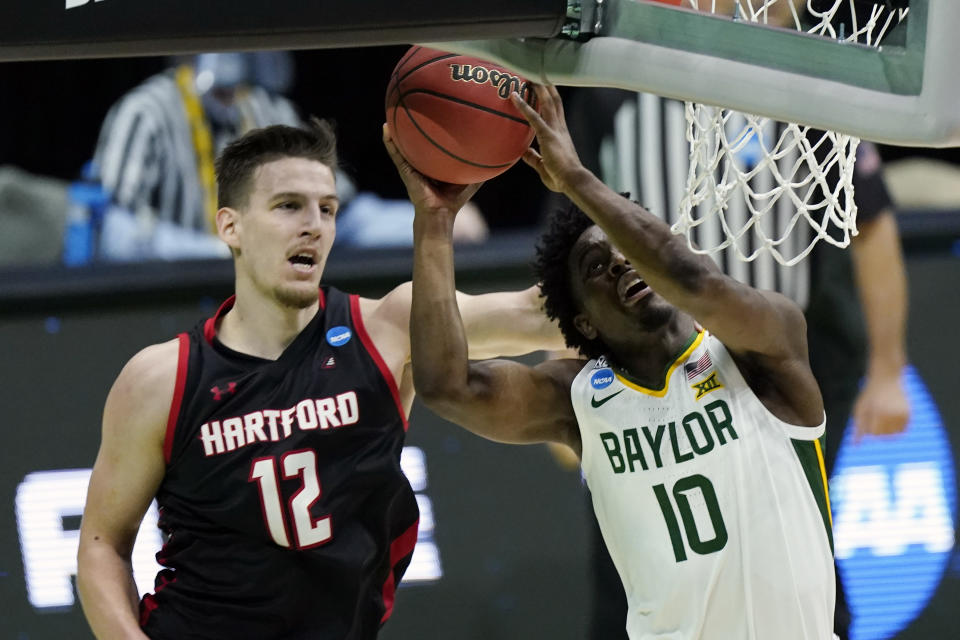 Baylor's Adam Flagler (10) drives against Hartford's Miroslav Stafl (12) during the second half of a college basketball game in the first round of the NCAA tournament at Lucas Oil Stadium in Indianapolis Friday, March 19, 2021, in Indianapolis, Tenn. (AP Photo/Mark Humphrey)