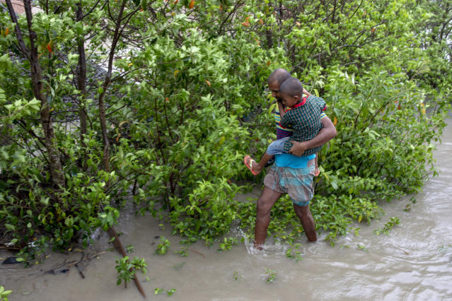 """DAKOP, KHULNA, BANGLADESH - 2020/05/20: A man with his son walks through water after crosses the river by boat immediately before Cyclone Amphan hits Bangladesh costal area in Khulna. Authorities have scrambled to evacuate low lying areas in the path of Amphan, which is only the second """"super cyclone"""" to form in the northeastern Indian Ocean since records began. (Photo by K M Asad/LightRocket via Getty Images)"""