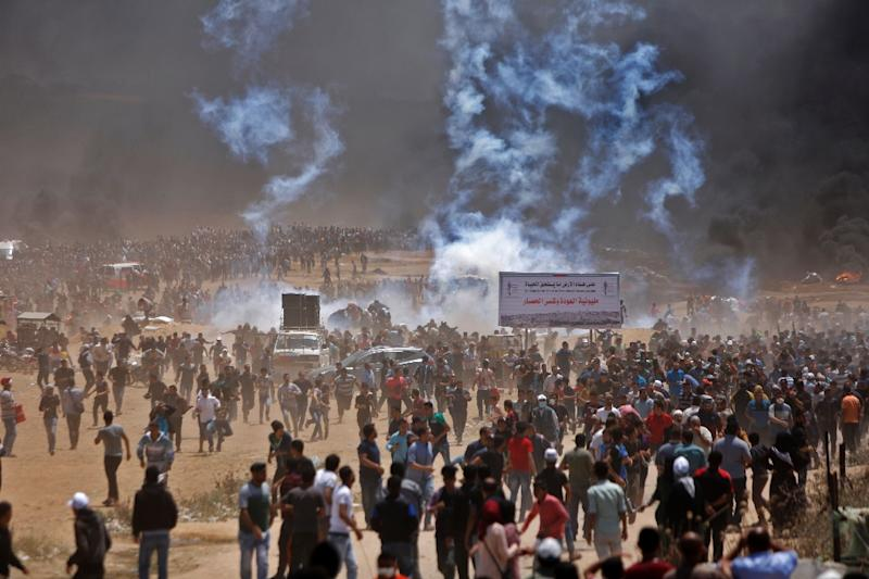 Palestinians run for cover from tear gas during clashes with Israeli security forces near the border between Israel and the Gaza Strip, east of Jabalia on May 14, 2018 (AFP Photo/MOHAMMED ABED)