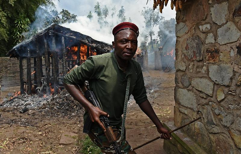 A soldier runs from a house set on fire by protestors opposed to the Burundian president's bid to stand for a third term in Butagazwa, Mugongomanga, some 30km east of Bujumbura, on June 5, 2015 (AFP Photo/Carl De Souza)