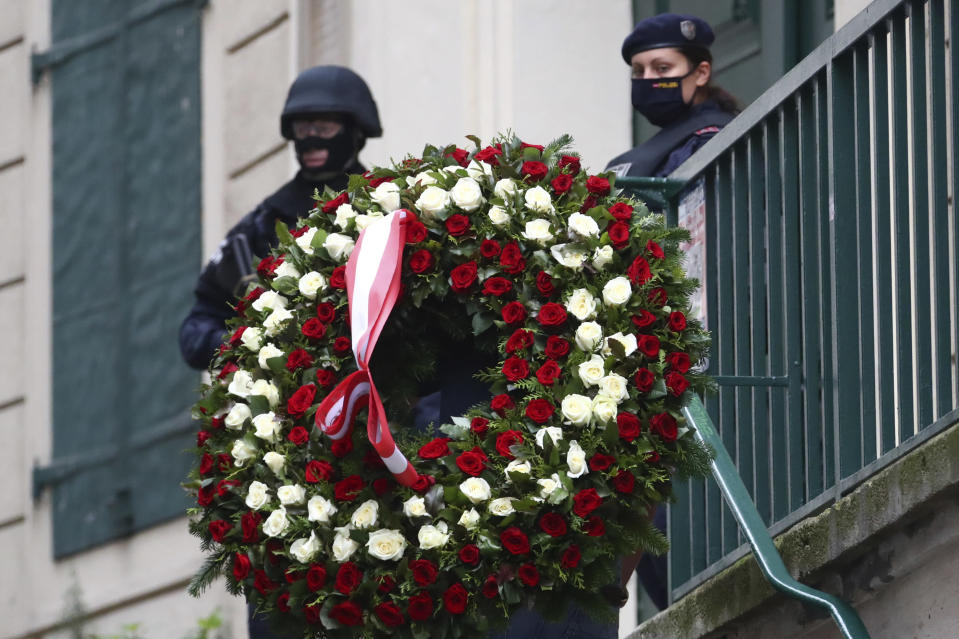 A man carries a wreath as he walks past police officers in Vienna, Austria, Tuesday, Nov. 3, 2020. Police in the Austrian capital said several shots were fired shortly after 8 p.m. local time on Monday, Nov. 2, in a lively street in the city center of Vienna. Austria's top security official said authorities believe there were several gunmen involved and that a police operation was still ongoing. (AP Photo/Matthias Schrader)