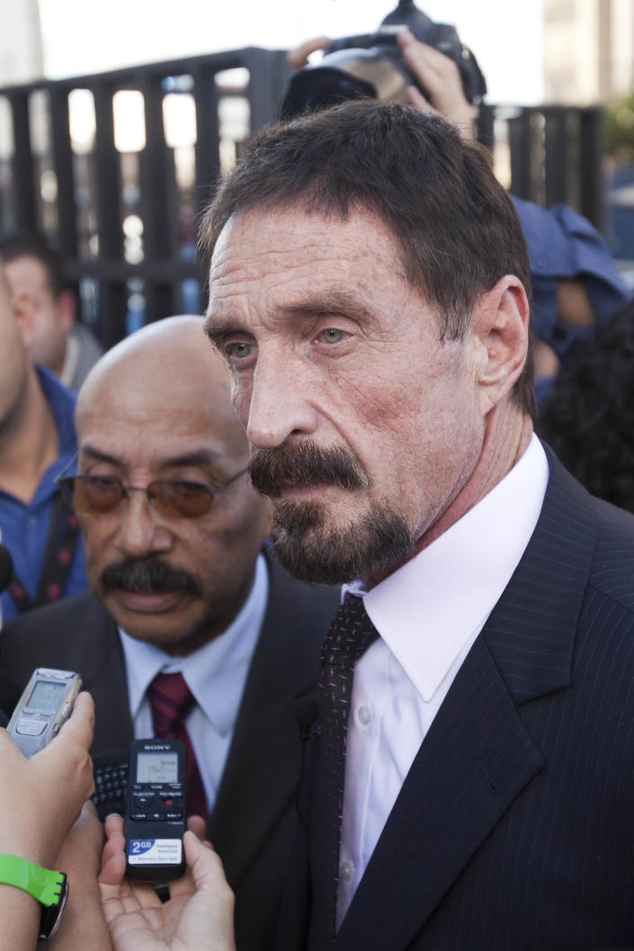 """Software company founder John McAfee, front, speaks to media members outside the Supreme Court in Guatemala City, Tuesday, Dec. 4, 2012. McAfee, 67, who has been identified as a """"person of interest"""" in the killing of his neighbor in Belize, 52-year-old Gregory Faull, has surfaced in public for the first time in weeks, saying Tuesday that he plans to ask for asylum in Guatemala because he fears persecution in Belize. (AP Photo/Moises Castillo)"""
