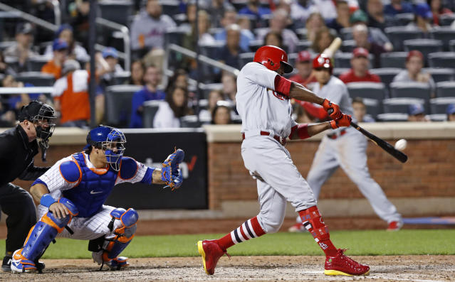 St. Louis Cardinals' Dexter Fowler hits a three-run home run during the eighth inning of the team's baseball game against the New York Mets, Friday, June 14, 2019, in New York. Mets catcher Wilson Ramos is behind the plate, as is home plate umpire Jeff Kellogg. (AP Photo/Kathy Willens)