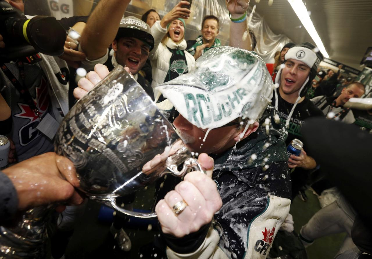 Saskatchewan Premier Brad Wall drinks from the Grey Cup after the Saskatchewan Roughriders defeated the Hamilton Tiger-Cats in the CFL's 101st Grey Cup championship football game in Regina, Saskatchewan November 24, 2013. REUTERS/Mark Blinch (CANADA - Tags: SPORT FOOTBALL)