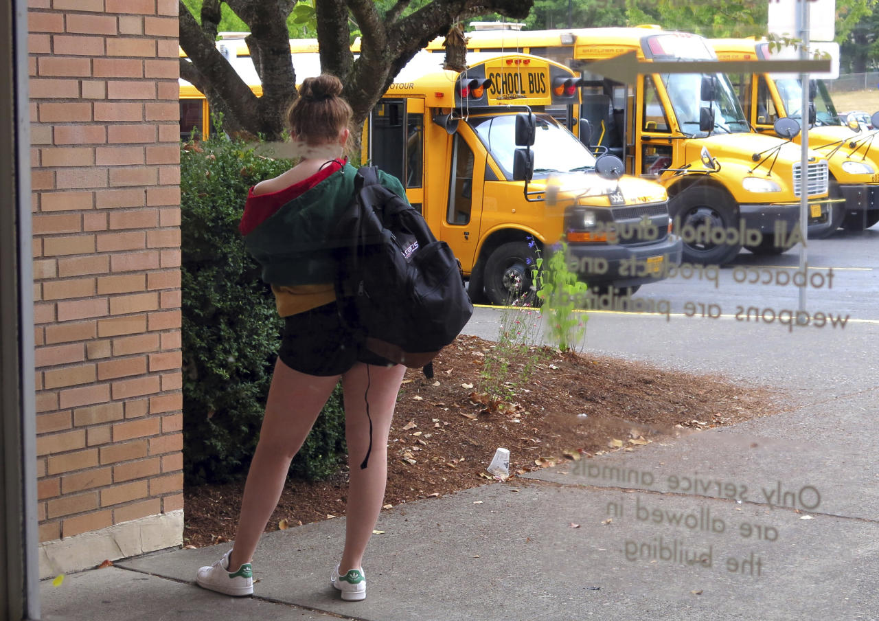 In this Sept. 7, 2018 photo, a student at Grant High School in Portland, Ore., waits for a ride after school. Portland Public Schools relaxed its dress code in 2016 after student complaints that the rules unfairly targeted female students and sexualized their fashion choices. (AP Photo/Gillian Flaccus)