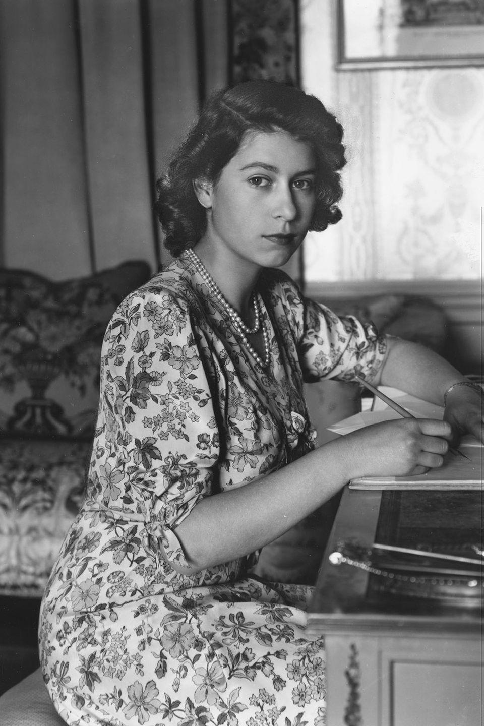 <p>The princess wore a floral-printed dress and pearls as she wrote a note at her desk in Windsor Castle. </p>