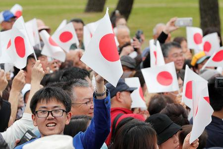 People wave Japanese flags as they wait for Emperor Naruhito outside the Imperial Palace in Tokyo, Japan May 1, 2019. REUTERS/Kim Kyung-Hoon