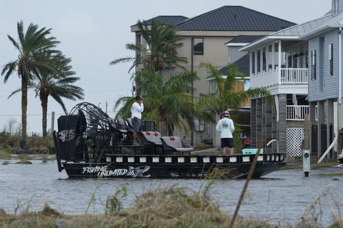 In the aftermath of Hurricane Ida, people on a airboat survey the damage to homes Wednesday, Sept. 1, 2021, in Myrtle Grove, La. (AP Photo/Steve Helber)