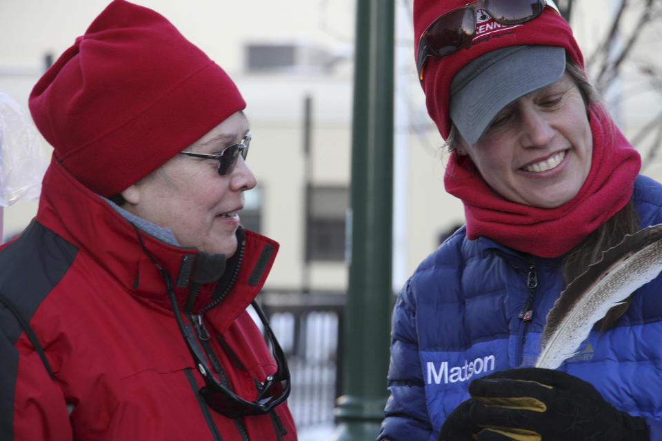 In this Saturday, March 2, 2019 photo, musher Aliy Zirkle, right, examines a feather given to her as a gift by a fan at the ceremonial start of the Iditarod Trail Sled Dog Race in Anchorage, Alaska. Zirkle was leading the race early Thursday, and was the first musher to reach the halfway point of the race when she pulled into the checkpoint in the ghost town of Iditarod, Alaska. (AP Photo/Mark Thiessen)