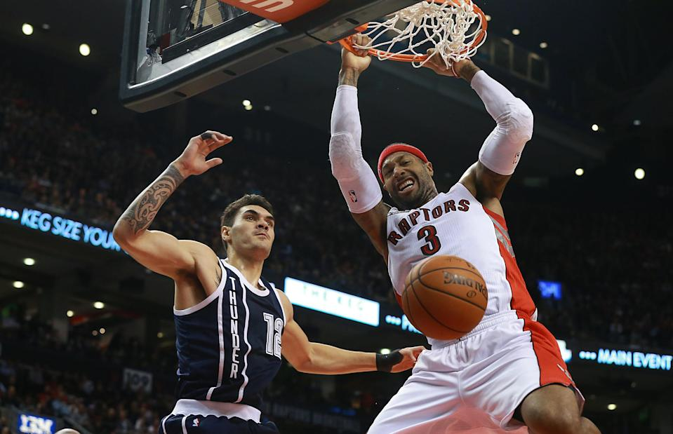 James Johnson (R) of the Toronto Raptors drives past Steven Adams of the Oklahoma City Thunder to dunk the ball during their NBA game at Air Canada Centre in Toronto, on November 4, 2014 (AFP Photo/Dave Sandford)