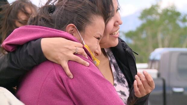 Summer Twoyoungmen, right, embraces Darvette Lefthand, left, after her speech at an anti-drug march in Morley, Alta., on Saturday. Both women are moms to young children, who say they want their children to grow up in a safe community free of predatory drug dealers.