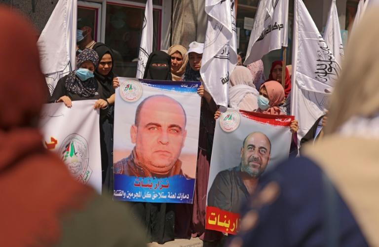Women hold up posters depicting late Palestinian human rights activist Nizar Banat during a Gaza City protest days after he died during a violent arrest