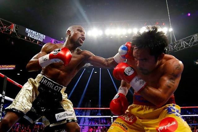 "Floyd Mayweather Jr. throws a punch at Manny Pacquiao during their 2015 ""Fight of the Century"" (AFP Photo/AL BELLO)"