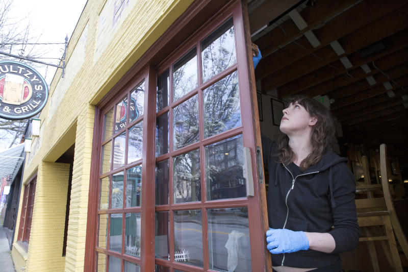 SEATTLE, WA - MARCH 24: Emily Scully, whose family owns Shultzys Bar and Grill stains trim around the windows on March 24, 2020 in Seattle, Washington. Washington State Governor Jay Inslee issued a Stay at Home order to begin March 25, requiring everyone in the state to stay home for at least two weeks and all non-essential businesses to shut down to help stem the spread of coronavirus (COVID-19). Scully says her family closed the business on March 16 when restaurants were ordered closed and they're using the time to paint and clean. (Photo by Karen Ducey/Getty Images)