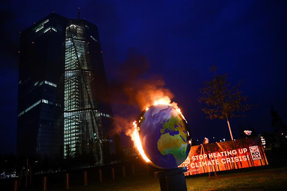 Protesters hold a banner as a paper made globe is seen burning during a demonstration against the fossil fuel industry, in front of the headquarters of the European Central Bank (ECB), in Frankfurt, Germany, October 21, 2020. REUTERS/Kai Pfaffenbach