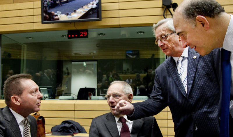 Luxembourg's Prime Minister Jean-Claude Juncker, second right, playfully gestures toward Greek Finance Minister Yannis Stournaras, left, during a meeting of eurogroup finance ministers in Brussels on Thursday, Dec. 13, 2012. The European Union on Thursday took a major step towards one of the most important transfers of financial authority away from national capitals when its member states agreed to create a single supervisor for their banks. At center is German Finance Minister Wolfgang Schaeuble, and at right is French Finance Minister Pierre Moscovici. (AP Photo/Virginia Mayo)