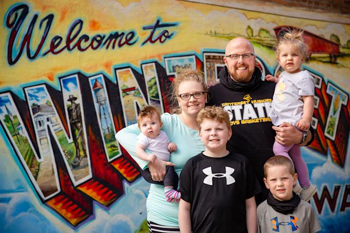 Sarah and Corey Bradley with their kids, Carsyn, 3 months, Camden, 9, Corbin, 5, and Cayson, 2, on the square in Winterset, Iowa, on May 10, 2021. The Bradleys had a baby during the pandemic, but they also contracted COVID-19 just a few weeks before Sarah gave birth.