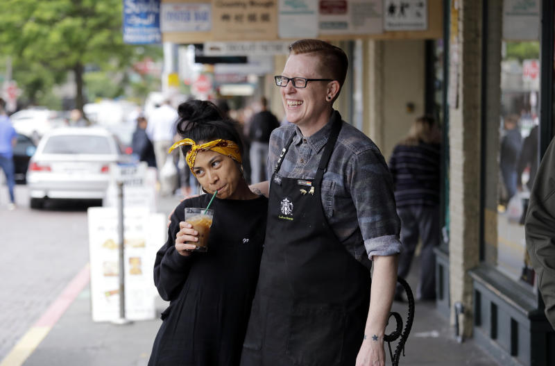 Barista Sarah Dacuno, left, is embraced by assistant manager Lindsey Pringle outside the Pike Place Market Starbucks, commonly referred to as the original Starbucks, as they prepare to close it for the day Tuesday, May 29, 2018, in Seattle. The first Starbucks cafe was located nearby in the early 1970's. Starbucks closed more than 8,000 stores nationwide on Tuesday to conduct anti-bias training, the next of many steps the company is taking to try to restore its tarnished image as a hangout where all are welcome. (AP Photo/Elaine Thompson)