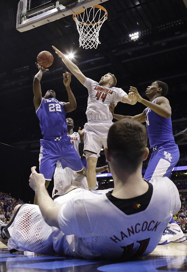 Kentucky's Alex Poythress (22) tries to shoot past Louisville's Stephan Van Treese (44) as Luke Hancock lays on the ground during the second half of an NCAA Midwest Regional semifinal college basketball tournament game Saturday, March 29, 2014, in Indianapolis. (AP Photo/David J. Phillip)
