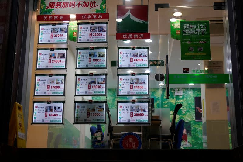 A real estate agency's window displays cards advertising apartments, along a street in Shanghai