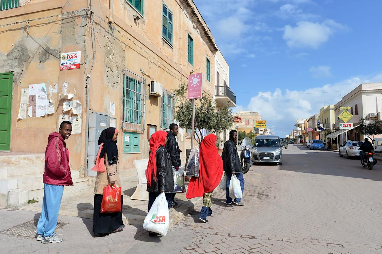 Men and women refugees make a walk in the center of Lampedusa, on February 19, 2015. Authorities on the Italian island of Lampedusa struggled to cope with a huge influx of newly-arrived migrants as aid organisations warned the Libya crisis means thousands more could be on their way. Officials on the tiny island south of Sicily were trying to process more than 1,200 exhausted, often traumatised and ill Africans in a reception centre designed for less than a third of that number. AFP PHOTO / ALBERTO PIZZOLI (Photo credit should read ALBERTO PIZZOLI/AFP/Getty Images)