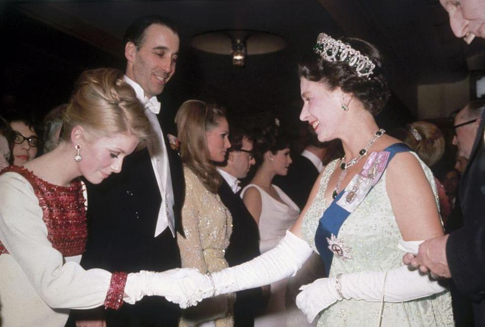 <p>French actress Catherine Deneuve greeted Queen Elizabeth with a respectful curtsy, which is all fine and good, but can we talk about her dress?! The red beaded detailing. The matching earrings. It's all so good.</p>