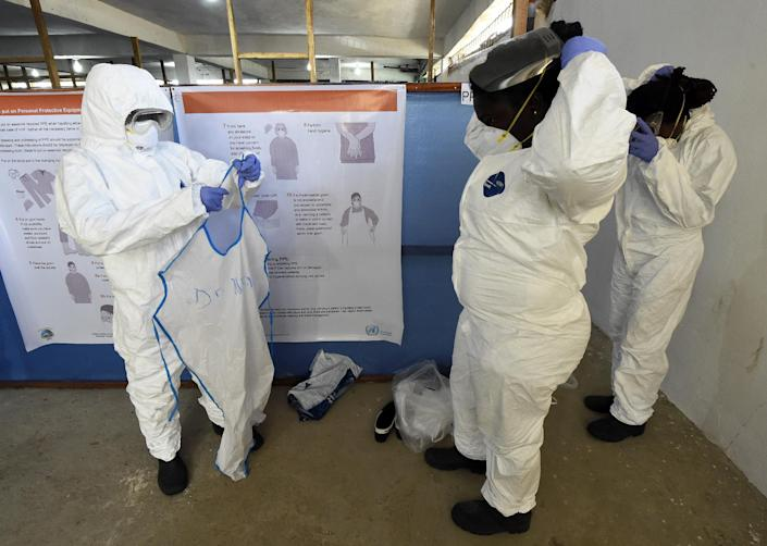 Health workers put on their protective clothing at a training center for the Ebola virus at a World Health Organization health center in the Liberian capital Monrovia, on October 3, 2014 (AFP Photo/Pascal Guyot)