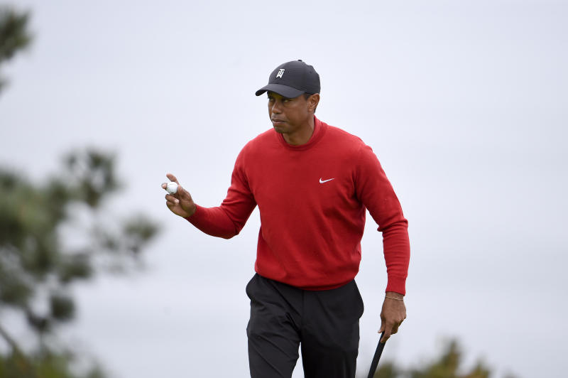 Tiger Woods holds up the ball after putting the fourth hole of the South Course at Torrey Pines Golf Course during the final round of the Farmers Insurance golf tournament Sunday, Jan. 26, 2020, in San Diego. (AP Photo/Denis Poroy)