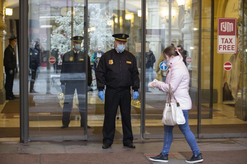 Security guards wearing face masks and gloves to protect from coronavirus, stand at an entrance of the GUM, State Department store after reopening in Moscow, Russia, on Monday, June 1, 2020. Monday's reopening of retail stores along with dry cleaners and repair shops comes as the pace of contagion has stabilized in the Russian capital that has accounted for about half of the nation's infections. (AP Photo/Alexander Zemlianichenko Jr)