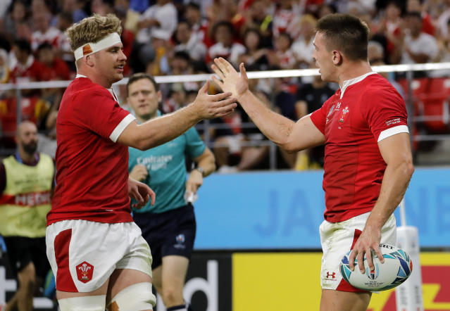 Wales Josh Adams, right, is congratulated by teammate Aaron Wainwright after scoring his side's third try during the Rugby World Cup Pool D game between Wales and Georgia at Toyota City Stadium, Toyota City, Japan, Monday, Sept. 23, 2019. (AP Photo/Christophe Ena)