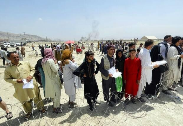 Hundreds of people gather outside the international airport in Kabul, Afghanistan. Desperate crowds have been trying to flee the country, now under Taliban rule.  (The Associated Press - image credit)