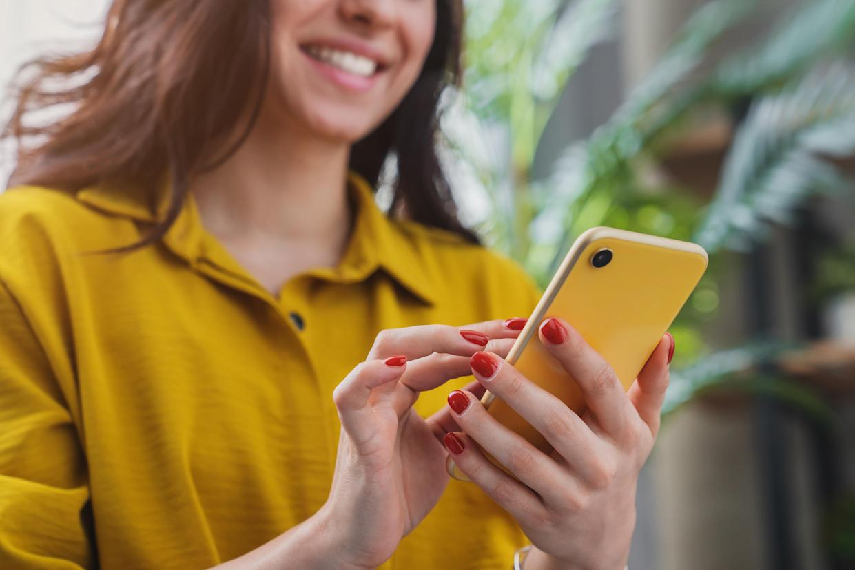 Cropped image of happy girl using smartphone device while chilling at home