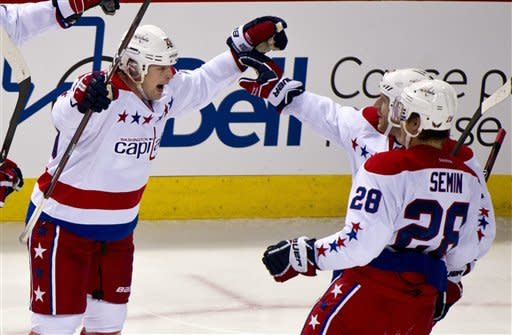 Washington Capitals' Matt Hendricks, left, celebrates his goal against the Montreal Canadiens with teammates Alexander Semin and Brooks Laich, rear, during third period NHL hockey action, Saturday, Feb. 4, 2012 in Montreal. (AP Photo/The Canadian Press, Paul Chiasson)