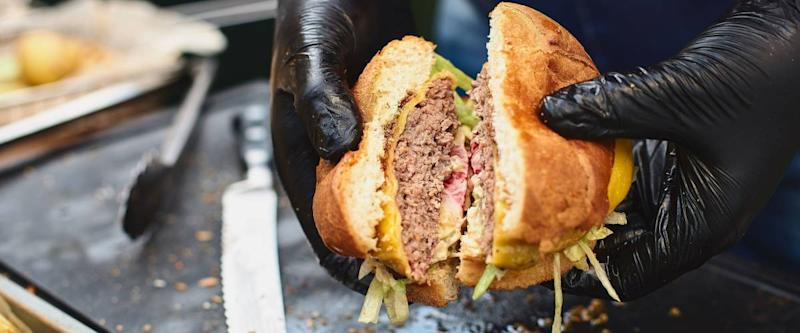 Close up of appetising beef burger. Chef's hands divide into half cooked hamburgers from beef. Street food ready to serve on a food stall. Chef cooks an American tasty hamburger.