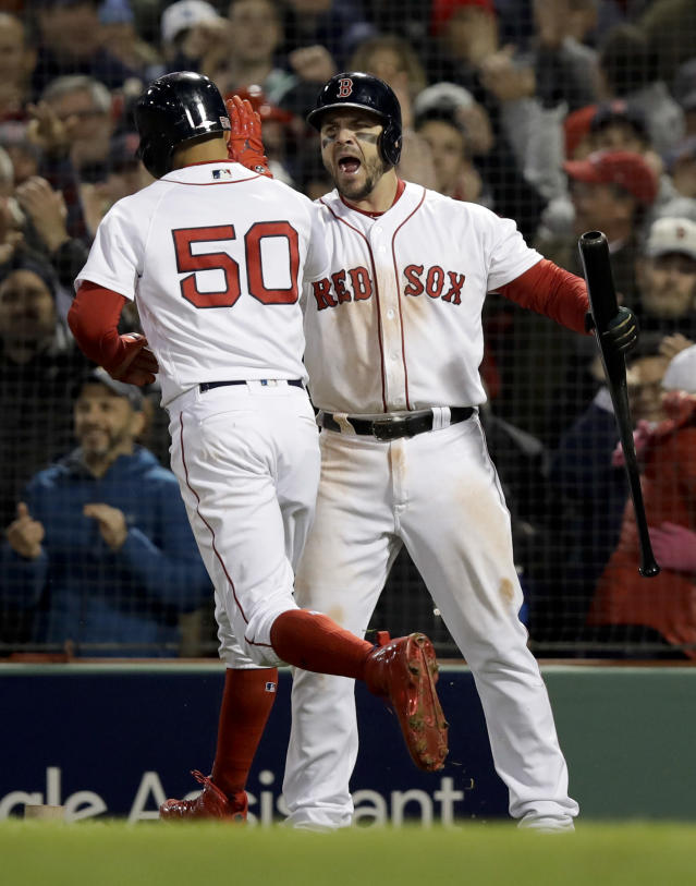 Boston Red Sox's Mookie Betts celebrates after scoring on a passes ball with Steve Pearce during the seventh inning in Game 2 of a baseball American League Championship Series against the Houston Astros on Sunday, Oct. 14, 2018, in Boston. (AP Photo/Charles Krupa)