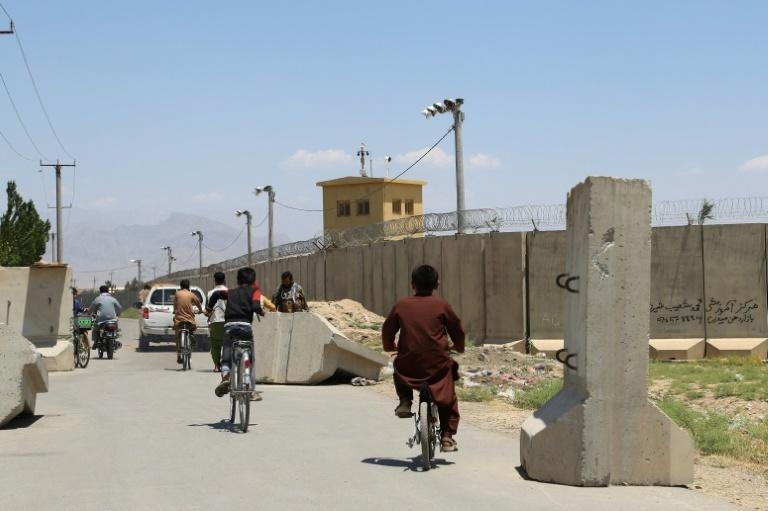 Children ride bicycles past a road checkpoint outside Bagram Air Base, after all US and NATO troops left