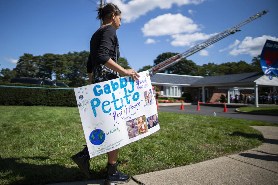 CORRECTS TO FUNERAL HOME VIEWING INSTEAD OF FUNERAL A woman carries a placard in honor of Petito as people attend the funeral home viewing of Gabby Petito at Moloney's Funeral Home in Holbrook, N.Y. Sunday, Sept. 26, 2021. (AP Photo/Eduardo Munoz Alvarez)