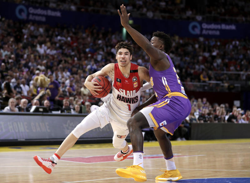 LaMelo Ball of the Illawarra Hawks drives past Jae'Sean Tate of the Sydney Kings during their game in the Australian Basketball League in Sydney, Sunday, Nov. 17, 2019. (AP Photo/Rick Rycroft)