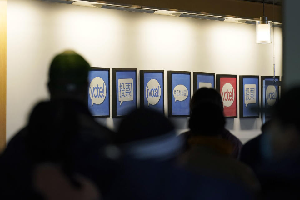 FILE - In this Oct. 23, 2020, file photo people lined up to vote or register to vote are shown next to signs in different languages at the King County election headquarters in Renton, Wash. Election officials are on high alert amid fears that U.S. polling stations could attract the same strain of partisan violence and civil unrest that erupted on American streets this year. (AP Photo/Ted S. Warren, File)