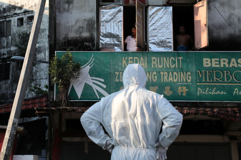 Residents look at a worker wearing a protective suit preparing for a disinfection operation, during the movement control order due to the outbreak of the coronavirus disease (COVID-19), in Kuala Lumpur