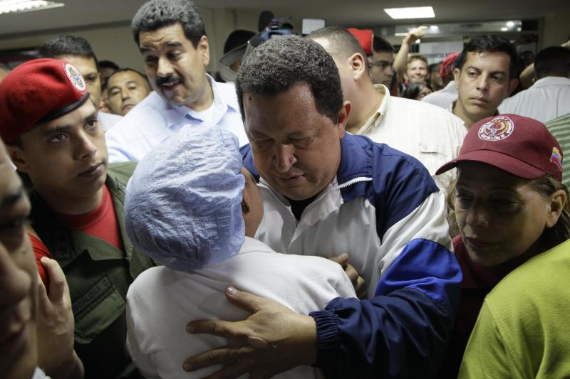 Venezuela's President Hugo Chavez, left, hugs a hospital worker, back to camera, during a visit to injured people after a refinery explosion at the Rafael Calle Sierra's public hospital in Punto Fijo, Venezuela, Monday, Aug. 27, 2012. A fire at the Amuay refinery spread to a third fuel tank on Monday nearly three days after a powerful explosion that killed 41 people and ignited the blaze, Vice President Elias Jaua said. (AP Photo/Ariana Cubillos)