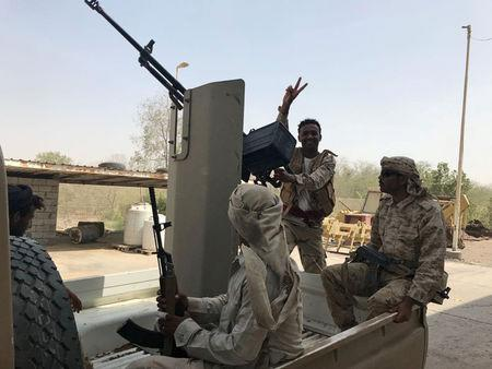 UAE-backed Yemeni soldiers ride on the back of a military patrol vehicle in the Red Sea port city of al-Mokha