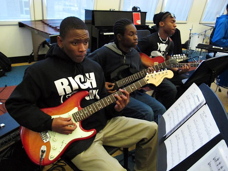 """In this March 22, 2013 photo, guitarists Kordae Maples, from left, Christian Nelson and Dallas Dodson rehearse a song at Stax Music Academy in Memphis, Tenn. The Stax Music Academy is an after-school program where teenagers from some of Memphis' poorest neighborhoods learn how to dance, sing and play instruments. The academy's students play annual shows in Memphis and have toured to Washington, Italy and Australia, helping spread the soulful """"Memphis Sound."""" (AP Photos/Adrian Sainz)"""