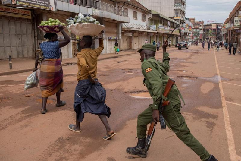 A police officer beats a female orange vendor on a street in Kampala, Uganda, on 26 March 2020